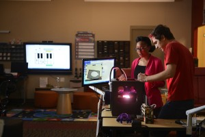 College of education students work in the library at Poe Hall with a Makerbot 3D printer. Photo by Marc Hall