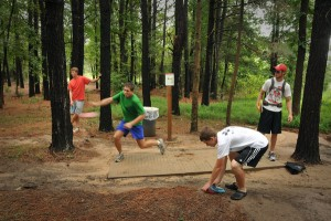 Disc golf team tosses out of the trees on Hole 8.